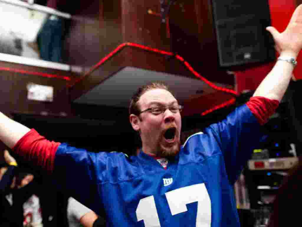 یکی از طرفداران کانادایی نیویورک جاینتز که در باری در نیویورک پیروزی تیمش را جشن گرفته
