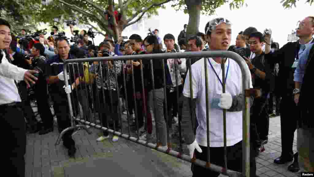 Colaboración entre un manifestante y un trabajador de la ciudad para retirar un obstáculo en el centro de Hong Kong.