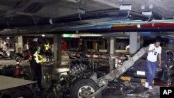Pihak berwajib memeriksa bangkai kendaraan yang dipasangi bom mobil di tempat parkir bawah tanah pusat perbelanjaan di Samui, Thailand (10/4).