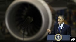 President Barack Obama speaks, Friday, Feb. 17, 2012, next to an airplane engine at the Boeing Company's 787 airplane assembly facility in Everett, Washington.