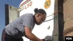 Rutendo Barna puts in the links of the horse to the trailer before departing to Malawi. (Photo: VOA)