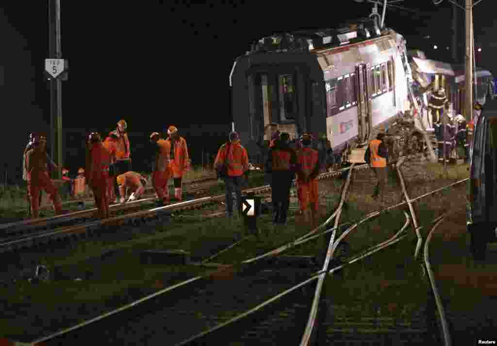 Swiss Federal Railways staff inspect the rails after removing carriages after a collision between two trains near Granges-pres-Marnand, Switzerland, July 29, 2013.