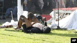 An injured person lies on his back at White City Stadium following a bomb blast last Saturday soon after President Emmerson Mnangagwa addressed members of the public.