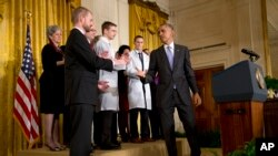 President Barack Obama turns to shake hands with Dr. Kent Brantly, 33, an Ebola survivor, after speaking at a White House event with American health care workers fighting Ebola, Oct. 29, 2014.