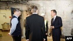 Thủ tướng Anh David Cameron (phải) đến thăm một siêu thị ở Salford bị hôi của