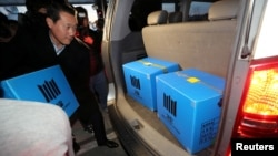 A prosecution investigation officer moves boxes carrying evidence seized at a branch office of National Pension Service in Jeonju, South Korea, Nov. 23, 2016.