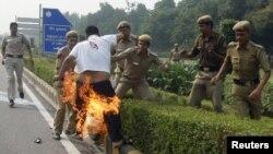 La policía intenta sofocar el fuego en un tibetano que se inmoló frente a la embajada China Nueva Delhi.