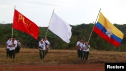 Fighters from Revolutionary Armed Forces of Colombia walk at the camp before the closing ceremony of a rebel congress near El Diamante in Yari Plains, Colombia, Sept. 23, 2016.