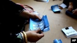 说明:2014年6月14日,首都喀布尔以东贾拉拉巴德一处投票站的阿富汗选举工作人员正在清点选票。