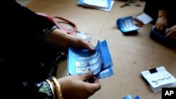 An Afghan election worker counts ballots at a polling station in Jalalabad, east of Kabul, Afghanistan, June 14, 2014.