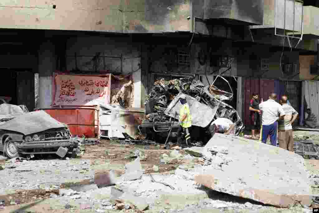 People inspect the scene of a car bomb attack in the Karrada neighborhood of Baghdad, Iraq, June 13, 2012.