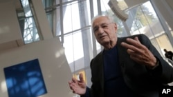 Frank Gehry, center, speaks to journalists during the press day at his latest creation, the Louis Vuitton Foundation art museum and cultural center, in Paris, Oct. 17, 2014.
