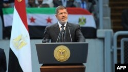 "In this handout picture Egyptian President Mohammed Morsi gives a speech to thousands of Islamists and Syrian opposition supporters during the ""support for Syria"" rally at Cairo stadium, June 15, 2013 in Cairo, Egypt. (Credit: Ho/Egyptian Presidency)"