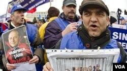 """Para demonstran anti-pemerintah di Bucharest membawa poster para pemimpin Rumania """"yang dipenjarakan"""" dengan berbagai slogan: """"Mereka harus diadili atas apa yang telah mereka curi (dari rakyat)."""""""