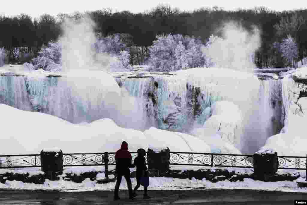 A couple looks out over the partially frozen American side of the Niagara Falls during sub-freezing temperatures in Niagara Falls, Ontario, Canada, Mar. 3, 2014.