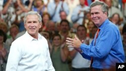 FILE - President George W. Bush, left, is introduced by his brother Florida Governor Jeb Bush (R) at a campaign rally, in Niceville, Florida, August 2004.