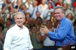 FILE - President George W. Bush, left, is introduced by his brother Florida Governor Jeb Bush, right, at a campaign rally, in Niceville, Florida, August 2004.