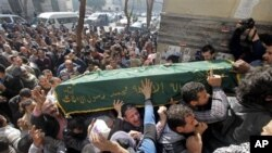 Keluarga dan kerabat mengangkat peti jenazah Mohammed el-Gindy menuju ke tempat pemakaman (4/2). El-Gindy, aktivis anti-pemerintah berusia 28 tahun meninggal dunia dalam tahanan polisi.