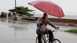 A man balances a child and umbrella on his bike as it rains during the approach of Hurricane Sandy in Manzanillo, Cuba, Oct. 24, 2012.