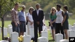 奥巴马总统和第一夫人米歇尔(右二)周六在阿灵顿国家公墓向在伊拉克和阿富汗战事中丧生的美国军方人员致意