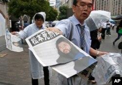 6일 일본 도쿄 시내에서 신문사 직원이 옴진리교 교주 아사하라 쇼코의 사형집행 소식이 1면에 난 신문을 시민들에게 건네고 있다.