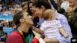 FILE - Michael Phelps celebrates winning his gold medal in the men's 200-meter butterfly with his fiance Nicole Johnson and baby Boomer during the swimming competitions on Aug. 9 at the 2016 Summer Games. Four month after getting married on June 13, the couple celebrated in Mexico.
