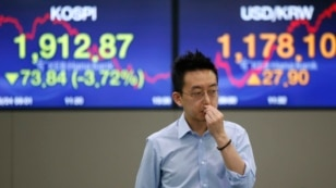 A currency trader walks by the screens showing the Korea Composite Stock Price Index (KOSPI), left, and the foreign exchange rate between U.S. Dollar and South Korean Won at the foreign exchange dealing room in Seoul, South Korea, June 24, 2016.