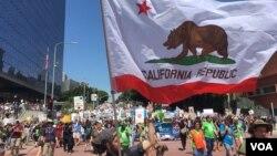 Un hombre eleva una bandera del estado de California durante la #MarchaPorLaCiencia. Foto: Arturo Martínez/VOA.