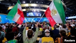 FILE - Supporters of the National Council of Resistance of Iran (NCRI) attend a rally in Villepinte, near Paris, France, June 30, 2018. A foiled attack had targeted the meeting.