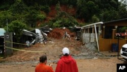 Civil Defense workers look the area where a couple was killed after their home was destroyed by a mudslide in Arraijan on the outskirts of Panama City, Tuesday, Nov. 22, 2016. Civil defense officials in Panama say the country has already seen three deaths blamed on late-season Tropical Storm Otto.