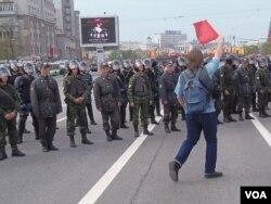 去年5月6日的反政府抗议中,一名示威者面对警察。(美国之音白桦拍摄)