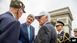 El secretario de Estado, John Kerry, saluda a veteranos estadounidenses de la II Guerra Mundial en París, frente al Arco del Triunfo, donde se encuentra la tumba al soldado desconocido.
