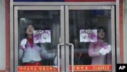 중국 단둥의 북한 식당에서 유리를 닦는 북한인 종업원들. (자료사진)