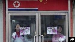 중국 단둥의 북한 식당에서 북한인 종업원들이 유리문을 닦고 있다. (자료사진)