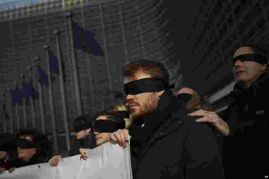 Blindfolded protesters against Brexit hold a banner outside the European Commission headquarters during a meeting between European Commission President Jean-Claude Juncker and British Prime Minister Theresa May in Brussels, Belgium.