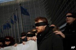 Blindfolded protesters against Brexit hold a banner outside the European Commission headquarters during a meeting between European Commission President Jean-Claude Juncker and British Prime Minister Theresa May in Brussels, Feb. 7, 2019.