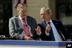 FILE - Former President George W. Bush, right, talks with his father, former President George H.W. Bush, during the dedication of the George W. Bush Presidential Center in Dallas, April 25, 2013. Father and son say they will not be endorsing Donald Trump'