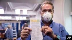 Novinar Brian Fuss pokazuje informacije o svom testu na COVID-19 nakon što se testirao u ambulanti Bijele kuće prije konferencije za novinare predsjednika Trumpa, 9. aprila 2020.