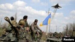 Binh sĩ Ukraine và máy bay chiến đấu bay ngang thị trấn Kramatorsk ở miền đông Ukraine, ngày 16/4/2014.