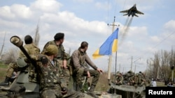 Ukrainian servicemen look at a Ukrainian military jet fly above them while they sit on top of armored personnel carriers in Kramatorsk, Ukraine, April 16, 2014.
