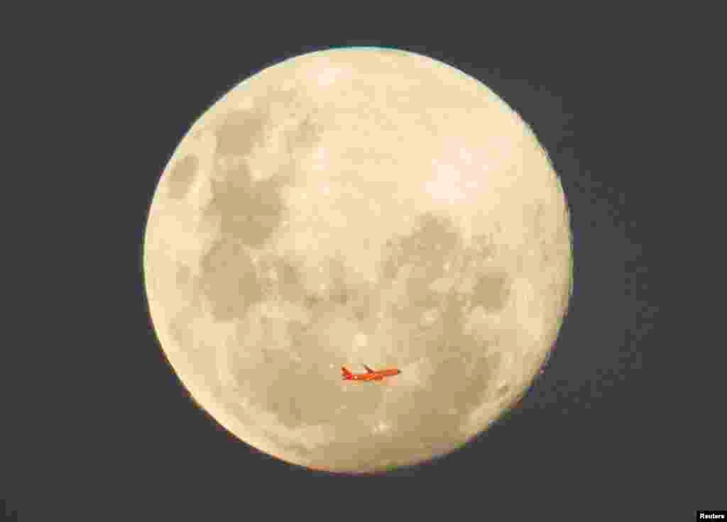 A Virgin Airlines commercial aircraft is illuminated by the setting sun in front of a full moon after taking off from Sydney Airport, Australia.
