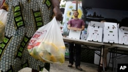 FILE - Seona Ngufor of Cameroon carries bags of squash.