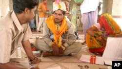 FILE - An employee of a women and children welfare department, left, urges a bridegroom to refrain from living with his minor bride till she attains the age of 18, after a marriage ceremony in Rajgarh, India, May 12, 2005.