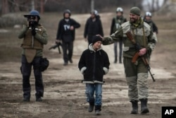 FILE - A Ukrainian serviceman speaks with a schoolboy in the village of Chermalyk, eastern Ukraine, Feb. 26, 2015.