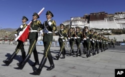 In this photo taken October 1, 2011, Chinese paramilitary police march during a flag raising ceremony near Potala Palace in Lhasa in northwestern China's Tibet province.