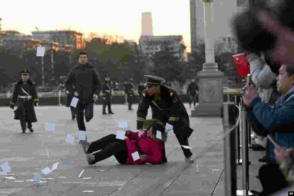 A petitioner is pushed to the ground by a paramilitary policeman after she ran into a cordoned off area near a national flag pole on Tiananmen Square and threw up flyers to protest her case of injustice, during a national flag raising ceremony early in the morning before the opening session of the annual National People's Congress at the nearby Great Hall of the People in Beijing, China.