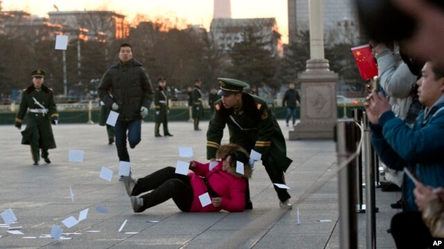 Cảnh sát Trung Quốc đè một người biểu tình xuống đất tại khu vực bị phong tỏa ở Quảng trường Thiên An Môn.