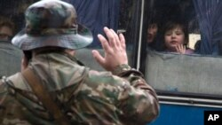 14일 우크라이나 동부 도네츠크에서 친러시아계 병사가 러시아로 떠나는 난민들에게 손을 흔들며 작별을 고하고 있다.