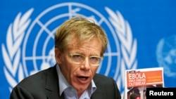世界卫生组织助理总干事在联合国日内瓦机构的记者会上手持埃博拉疫情报告