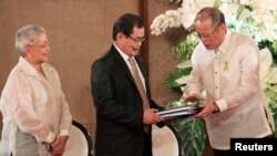 Philippine President Benigno Aquino hands over the draft Bangsamoro Basic Law (BBL) to Moro Islamic Liberation Front (MILF) chief negotiator Mohagher Iqbal (C) ahead of the turnover ceremony of the law at the presidential palace in Manila, September 10, 2